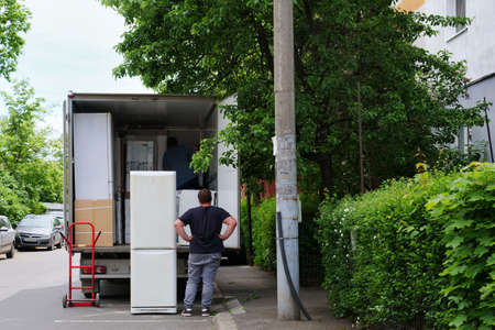Home delivery workers unload household appliances from a van during covid-19 pandemic lockdown in Cluj-Napoca, Romania on May 16, 2020