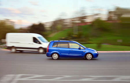 Fast driving blue car on the road at sunset with motion blur in Cluj-Napoca, Romania on April 23, 2015