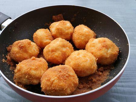 Breaded farmers cheese dumplings with roasted breadcrumbs in frying pan Фото со стока
