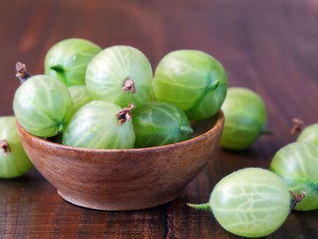 Green gooseberries in wooden bowl (Ribes uva-crispa) Фото со стока