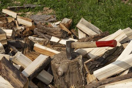 Log with the thrust axe against a heap of fire wood Stock Photo - 4709336