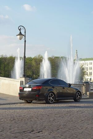 Close up of the car of black colour against a fountain Stock Photo