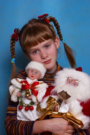 Portrait of the girl on a dark blue background with Christmas toys in hands