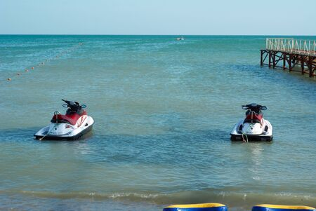 Two hydrocycles about a mooring on the sea Stock Photo