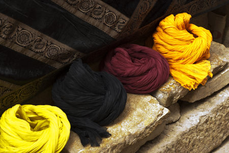 tapestry: Turbans on a sandstone wall with a tapestry background Stock Photo