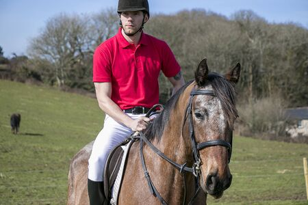 Handsome horse rider on horse in green field with other horse in background with blue sky and stone cottage Stock fotó
