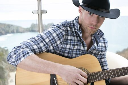Country and western, cowboy star playing guitar on hotel balcony with ocean in background Imagens