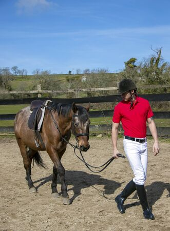 Handsome Male Horse Rider Walking Horse in paddock with white trousers, red polo shirt, black boots and helmet