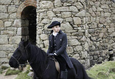 Beau mâle cheval cavalier régence costume Poldark du 18e siècle avec des ruines de mine d'étain et campagne en arrière-plan