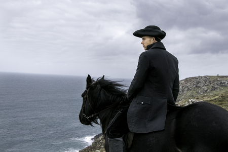 Handsome Male Horse Rider Regency 18th Century Poldark Costume with tin mine ruins and Atlantic ocean in background Banco de Imagens
