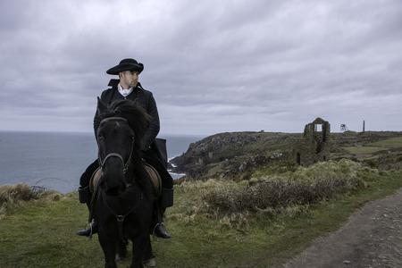 Beau mâle cheval cavalier régence costume Poldark du 18e siècle avec des ruines de mine d'étain et l'océan Atlantique en arrière-plan