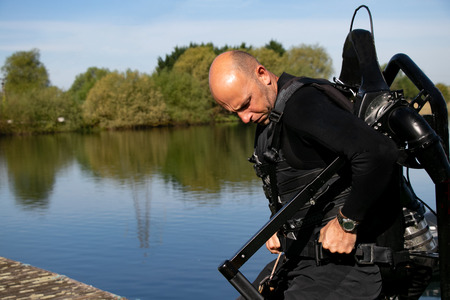 Male thrillseeker, water sports lover, athlete strapped to Jet Lev, levitation prepares to fly
