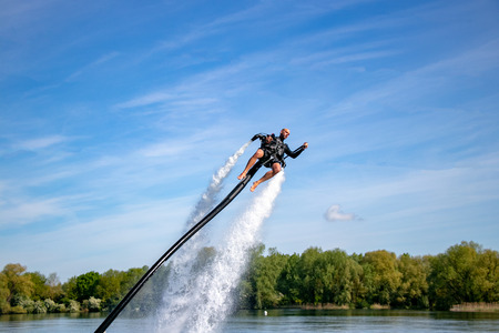 Thrillseeker, athlete strapped to Jet Lev, levitation soars into a blue sky with whispy clouds