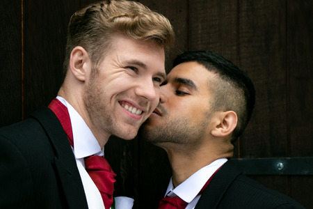 Gay wedding, grooms posing for as they hold hands and kiss outside village church