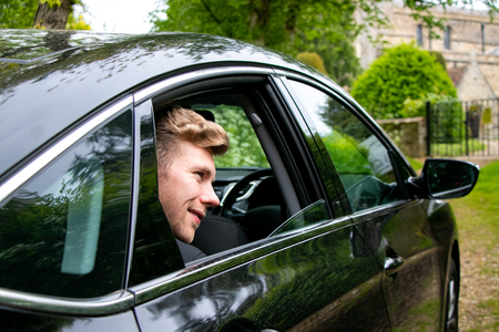 Groom arrives by car at village church on his wedding day Stock Photo