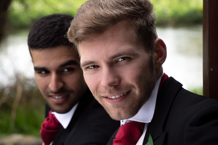 Gay couple of grooms pose for photographs by a lake on their wedding day
