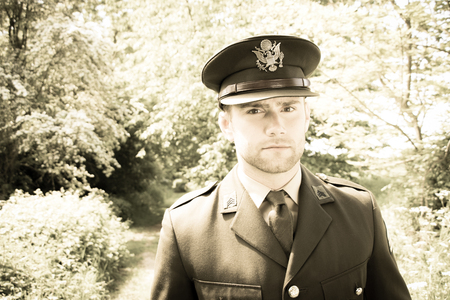 Handsome American WWII GI Army officer in uniform walking through woods