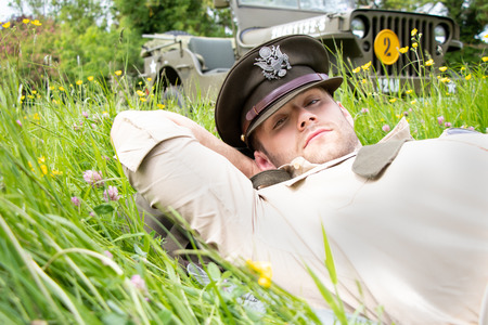 Handsome American Army officer in uniform relaxes in a meadow of flowers
