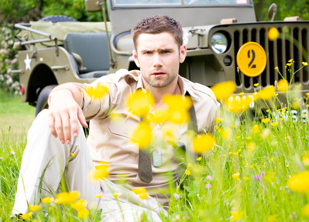 Handsome American WWII GI Army officer in uniform relaxes in a meadow of flowers in front of Willy Jeep Stock Photo
