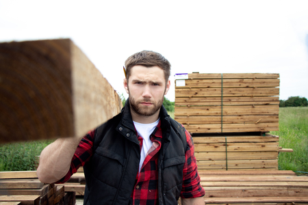 Lumber yard worker, carpenter, choosing, seclecting carrying timber planks