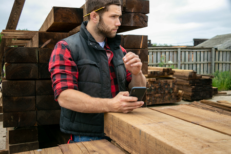 Lumber yard worker, carpenter at wood yard counts inventory with mobile device