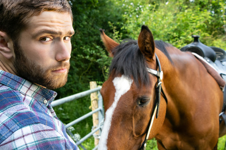 Handsome American cowboy, rider with checked, chequered shirt and jeans pets and loves his horse Stock Photo