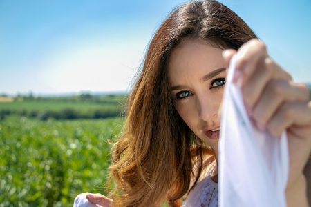 Beautiful woman, bride with blue eyes and brown hair walks through crop field on a sunny summers day