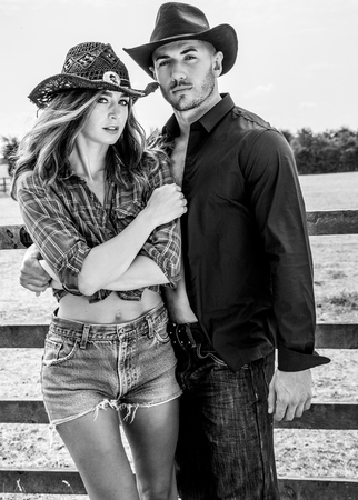 Cowboy and cowgirl on ranch farm fighting next to wooden face and fields