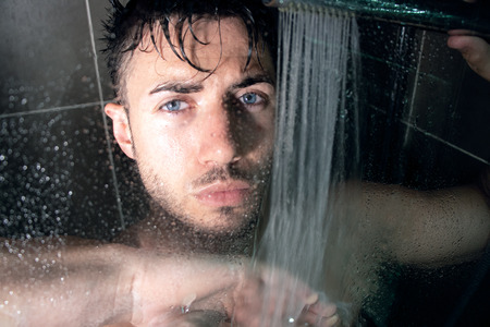 Hunky, handsome man, male with beard and muscular arms is wet in shower looking at camera