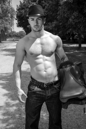 Sexy, handsome, hunky cowboy with hat and shirtless with pecs carrying saddle looking at camera