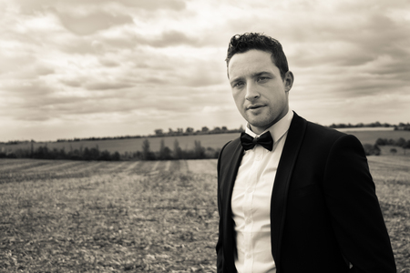 Man wearing tuxedo walks through field in countryside Imagens