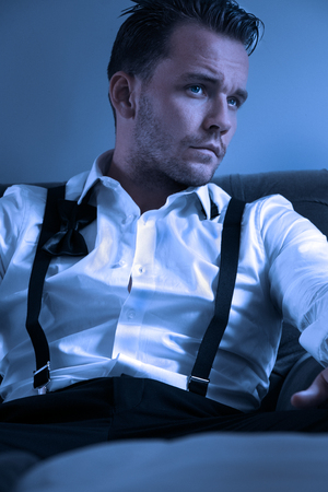 Man wearing tuxedo in hotel room, sitting in chair with loose tie Imagens