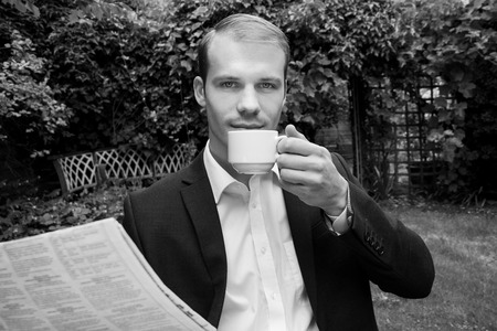 Man in suit enjoying early morning coffee in garden