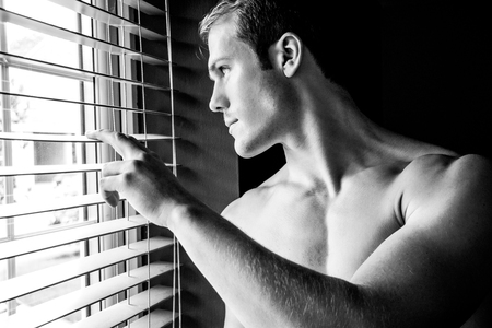 Good looking shirtless man with pecs looks out of window