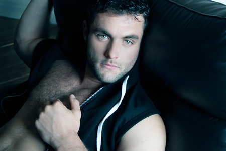 Good looking man with pecs and six pack abs sitting on armchair and looking at camera