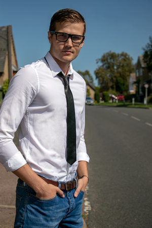 Good looking young excutive, business man on pavement of village Imagens
