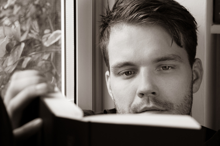 Good looking young man with black shirt reads book in window