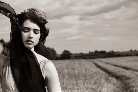 Beautiful stylish female in black and white classical portrait in field