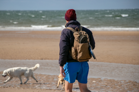 Man walks on beach with his dog and carrying rucksack