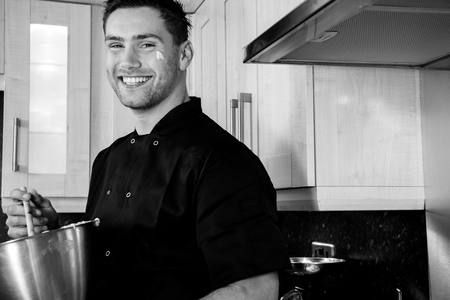 Good looking chef smiling as he stands in kitchen preparing for baking