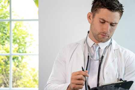 Good looking male doctor, gp, with stethoscope and clipboard