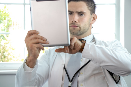 Good looking male doctor, gp, with stethoscope and tablet
