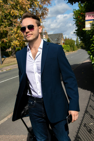 Good looking business man walking down sub urban country street