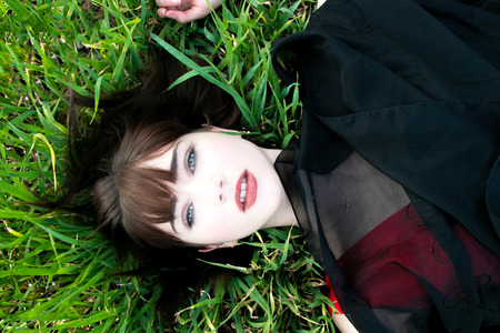 Overhead view of beautiful woman lying in grass looking at camera