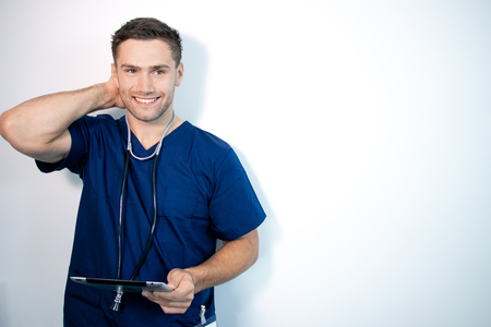 Good looking male doctor or nurse in blue scrubs, holding digital tablet and laughing