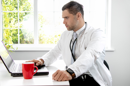 Good looking male doctor in white lab coat gp at desk looking at laptop computer