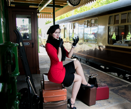 vintage attractive female wearing red dress and black beret, sitting on suitcases applying her makeup at train station Imagens