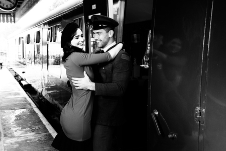 Vintage couple embracing and laughing on railway station platform as train arrives Imagens