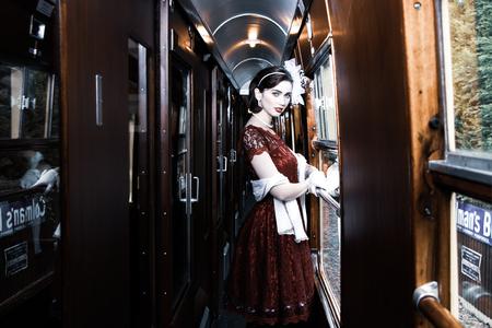 Beautiful woman dressed in red tea vintage tea dress on locomotive train
