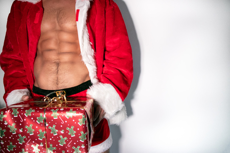 Six pack abs of fit santa with open jacket and carrying a gift
